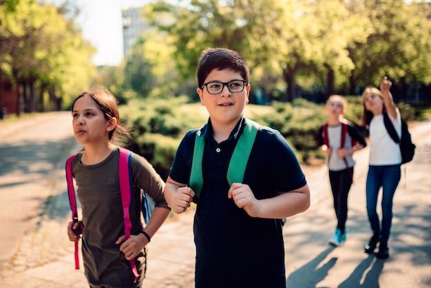 Compagni di classe al cortile della scuola che vanno a scuola