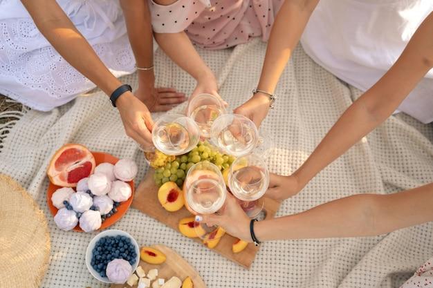 Compagnia di amiche si gode un picnic estivo e alza bicchieri di vino