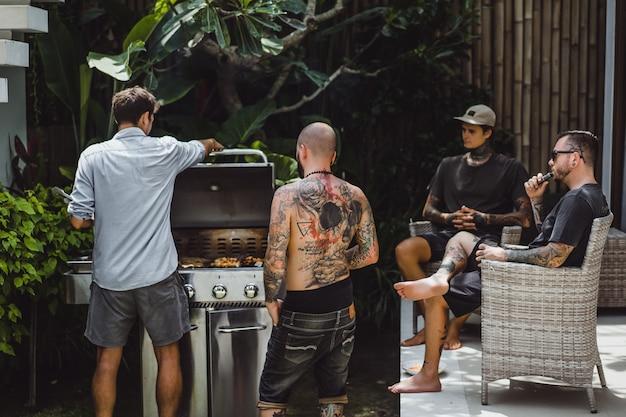 Compagnia di amici che cucinano barbecue all'aperto
