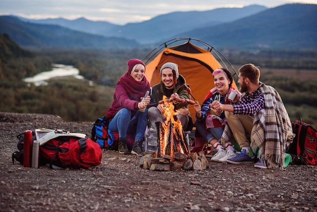 Compagnia di giovani amici che fanno un picnic in montagna