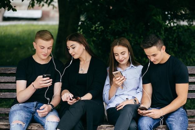 Compagnia di giovani amici con smartphone che camminano in città