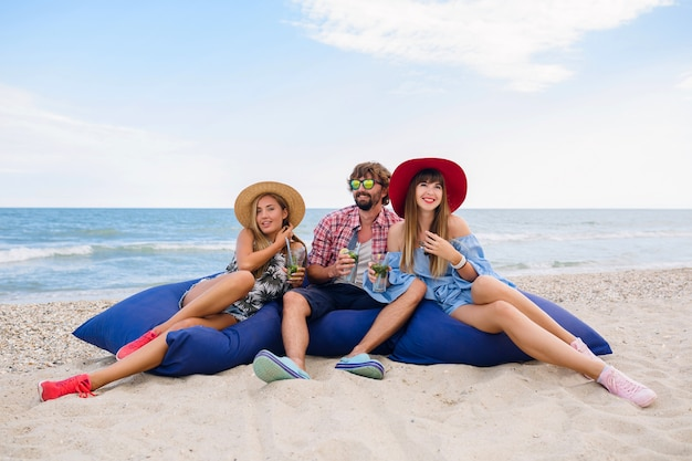 Compagnia di giovani hipster di amici felici in vacanza estiva seduti in spiaggia su sacchi di fagioli, bere cocktail mojito, divertirsi, rilassarsi, vita facile, sorridere, positivo