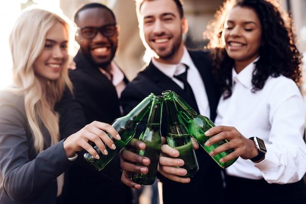 Compagnia di persone in strada con bevande alcoliche.