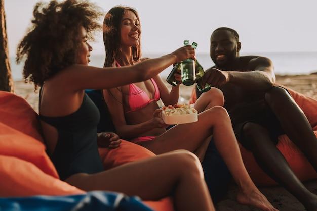 Compagnia multinazionale che beve birra sulla spiaggia.