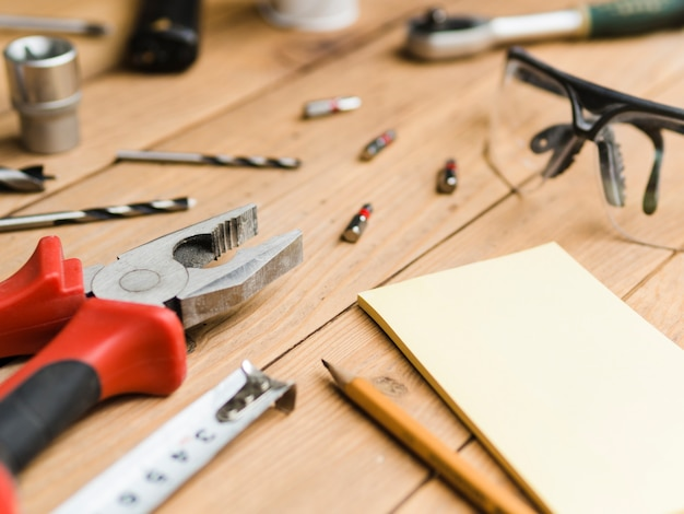 Compensato vicino agli oggetti del carpentiere sulla tavola