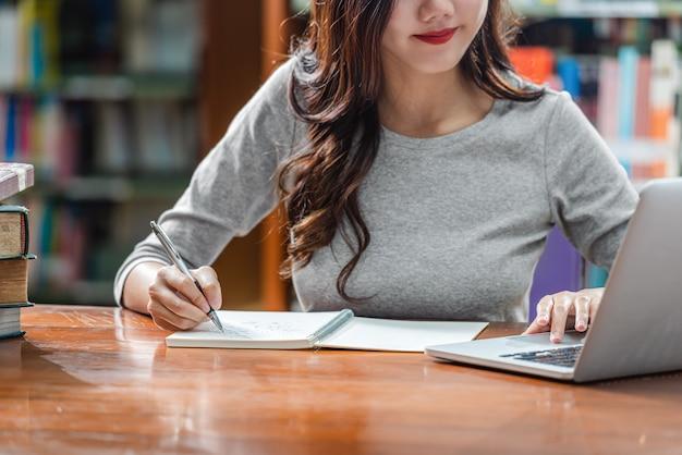 Compito asiatico giovane di scrittura della mano dello studente del primo piano e computer portatile usando tecnologia nella biblioteca dell'università