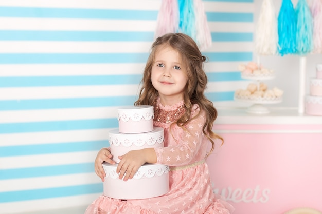 Compleanno! bella bambina che si siede con i regali. la barra del compleanno di candy. ritratto di un primo piano del viso del bambino.