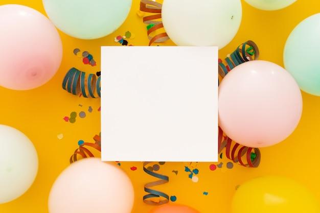 Compleanno con coriandoli e palloncini colorati su giallo