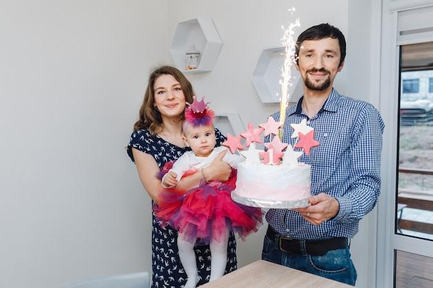 Compleanno di una bambina. mamma, papà e una piccola figlia carina con una torta