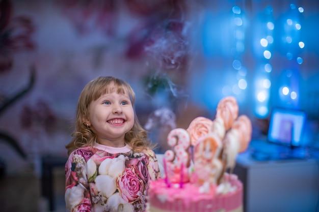 Compleanno. una bambina felice spegne le candeline sulla torta di compleanno.