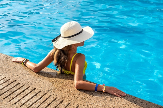 Completi giù il punto di vista della giovane donna che porta il cappello di paglia giallo che riposa nella piscina con chiara acqua blu il giorno soleggiato dell'estate.