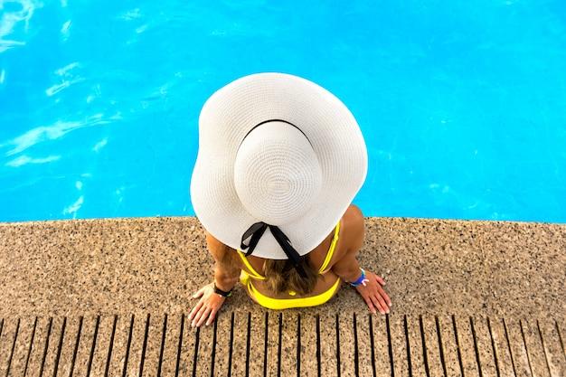 Completi giù il punto di vista della giovane donna che porta il cappello di paglia giallo che riposa vicino alla piscina con chiara acqua blu il giorno soleggiato dell'estate.