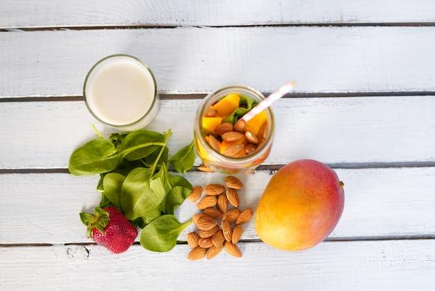 Componenti di vitamine green reach frullato con spinaci baby leaf, mango, latte di mandorla e fragola