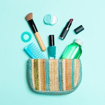 Componga i prodotti che si rovesciano dalla borsa dei cosmetici su fondo pastello blu con spazio vuoto