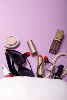 Componga la borsa con i cosmetici isolati su fondo rosa