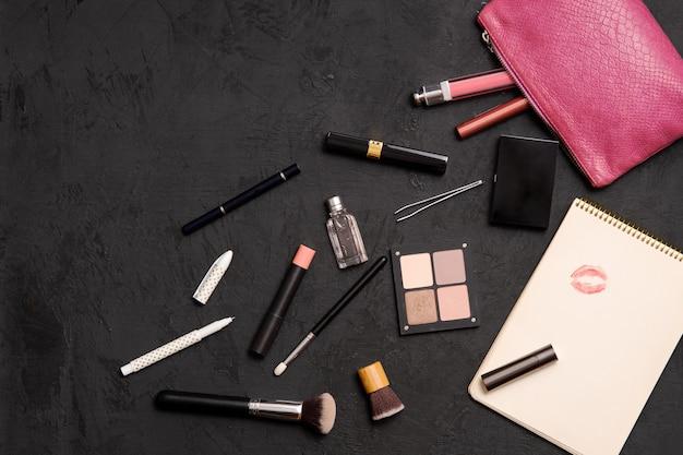 Componga la borsa con i cosmetici, le spazzole e il taccuino isolati su superficie nera