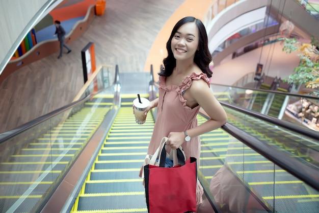 Comportamento urbano adolescente asiatico come lo shopping bere caffè in ascensore