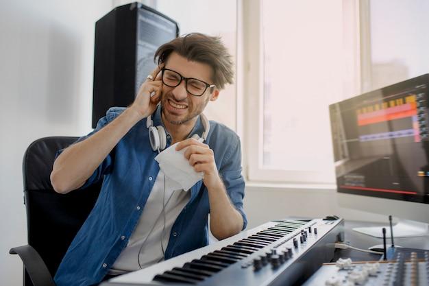 Compositore in studio di registrazione. tecnologia di produzione musicale,. l'uomo sta lavorando al mixer audio in studio di registrazione o dj in studio di radiodiffusione.