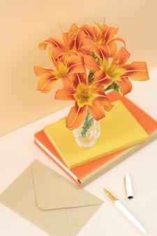 Composizione arancione con fiori e quaderni