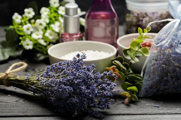Composizione aromatica di lavanda, erbe, cosmetici e sale su un tavolo scuro