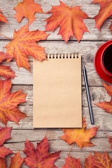 Composizione autunnale con area di lavoro con taccuino in bianco, matita, tazza di caffè rossa