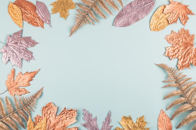 Composizione autunnale con cornice di foglie d'oro su sfondo blu pastello