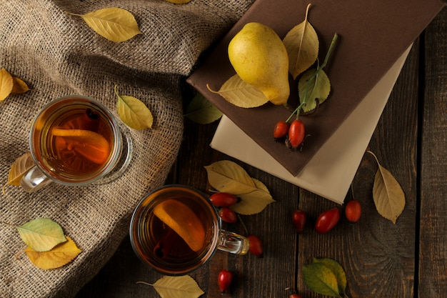 Composizione autunnale con foglie di tè giallo caldo e libri su un tavolo di legno marrone.