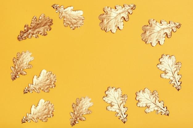 Composizione autunnale con foglie dorate sulla superficie della carta gialla
