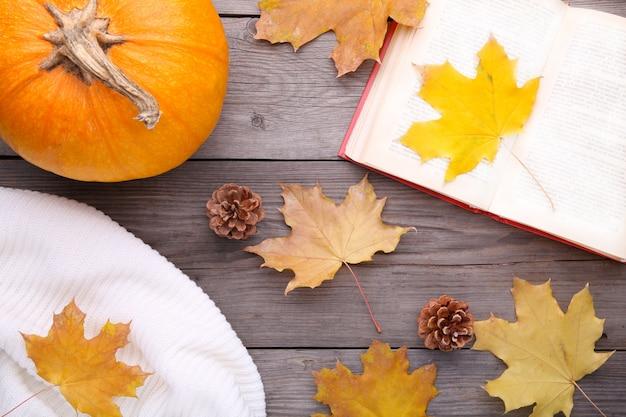 Composizione autunnale con il vecchio libro, zucca, maglione e foglie su un tavolo grigio