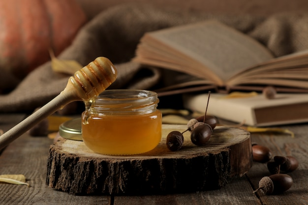 Composizione autunnale con miele su un tavolo di legno marrone