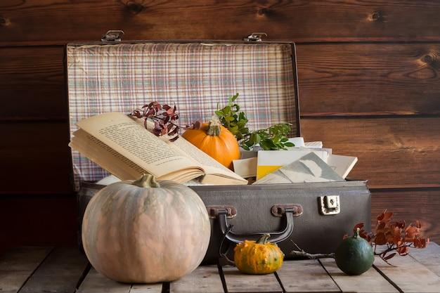 Composizione autunnale con zucche, valigia e libri
