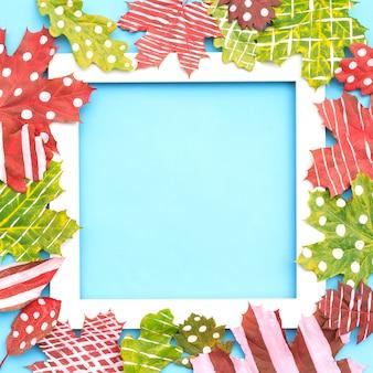 Composizione autunnale. cornice fatta di foglie secche creative acero, rovere dipinto con strisce, pois su sfondo blu.