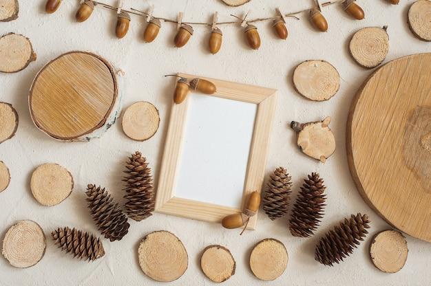 Composizione autunnale, cornice fatta di pigne, ghiande e piccoli ceppi di legno.