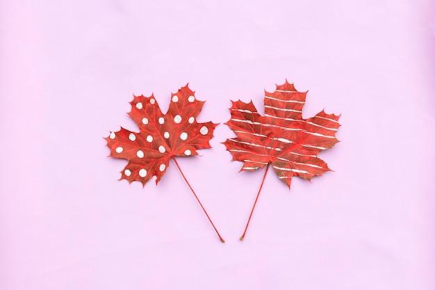 Composizione autunnale di foglie secche creative acero dipinto con strisce, pois su sfondo chiaro.
