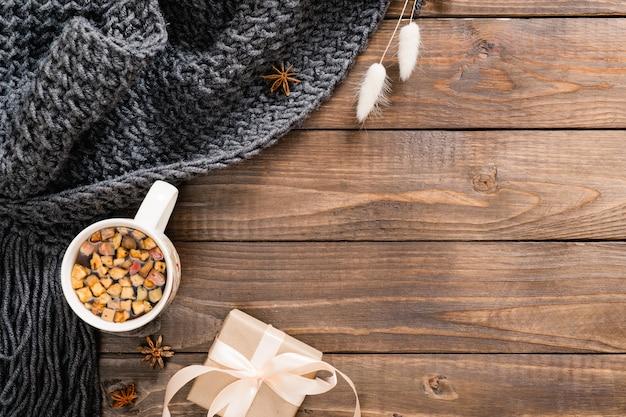 Composizione autunnale flatlay con tazza di tisana, plaid di lana, confezione regalo e fiori secchi su fondo di legno
