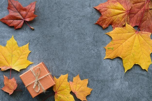 Composizione autunnale. foglie di acero e confezione regalo. vista piana, vista dall'alto