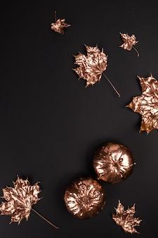 Composizione autunnale. foglie dipinte dorate autunnali naturali, zucche sul nero.
