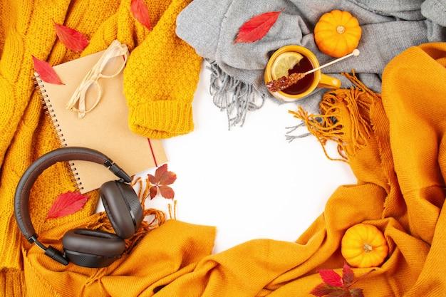 Composizione autunnale piatta con foglie autunnali, tazza di tè caldo e un caldo maglione di lana arancione
