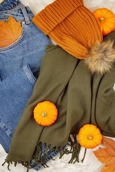 Composizione autunnale piatta con foglie autunnali, zucche, jeans e una sciarpa e un cappello di lana caldi