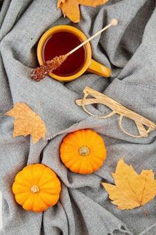 Composizione autunnale piatta con una tazza di tè e una calda sciarpa di lana