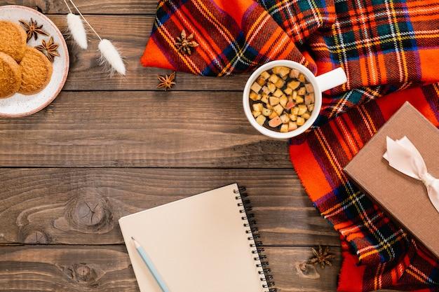 Composizione autunnale. sciarpa rossa moda donna, blocco note di carta, tazza di tisana, fiori secchi, biscotti, confezione regalo