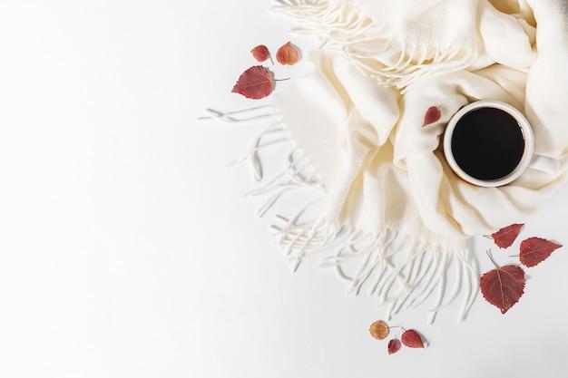 Composizione autunnale. tazza di caffè, sciarpa e foglie secche su sfondo grigio. vista piana, vista dall'alto, copia spazio