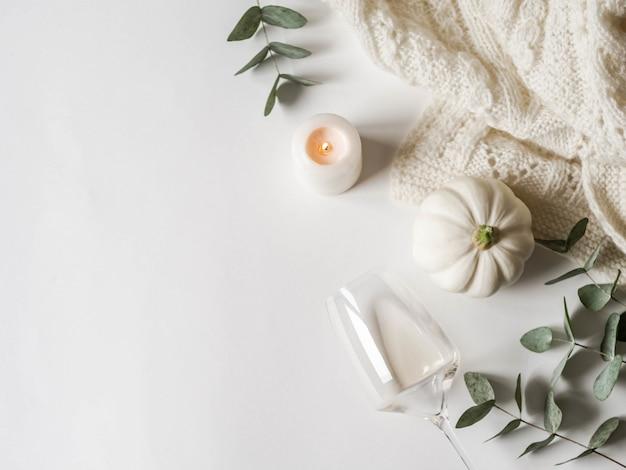Composizione bianca autunnale distesa piatta - zucche, candele, eucalipti, plaid, vino bianco.