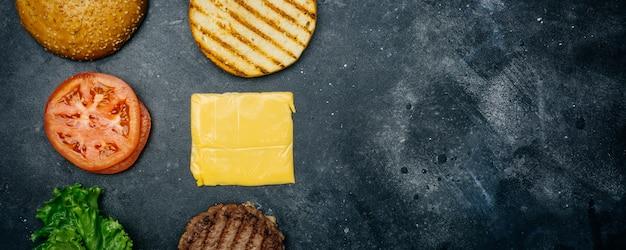 Composizione burger fatta in casa (ricetta). prodotti per il classico hamburger su uno sfondo scuro.