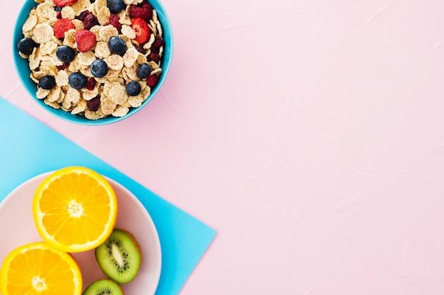 Composizione colazione estiva cereali, frutta su sfondo rosa pastello.