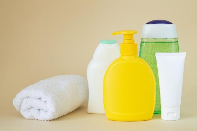 Composizione con asciugamano e bottiglie di plastica per la cura del corpo con copia spazio