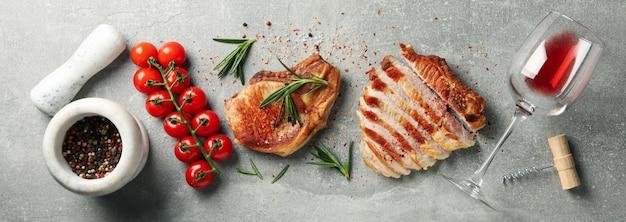 Composizione con bistecche fritte, vino e verdure. piatti alla griglia