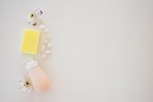 Composizione con bottiglia di sapone ghiaia e orchidee