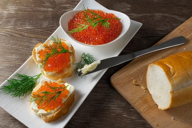 Composizione con caviale rosso sul pane con burro, ciotola bianca con caviale rosso e aneto sul vecchio tavolo di legno. cibo salutare. antipasto di pesce