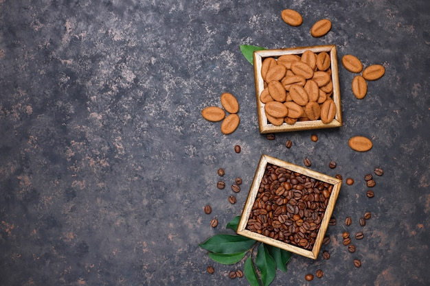 Composizione con chicchi di caffè tostati e biscotti a forma di chicco di caffè sulla superficie marrone scuro